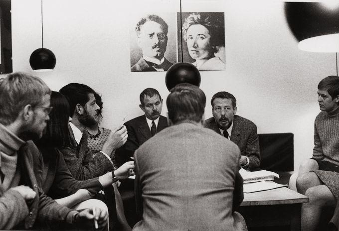 Sitzung im Republikanischen Club Köln unter den Portraits von Rosa Luxemburg und Karl Liebknecht. Auf dem Foto sind vier Frauen auszumachen.